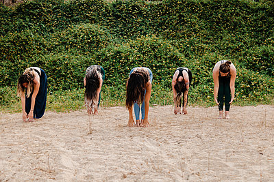 Women with yoga instructor practicing Uttanasana on sand against plants - p300m2256993 by Manu Reyes