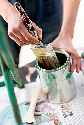 Human hand with paint brush and paint can, Stockholm, Sweden - p312m897116 by Johner