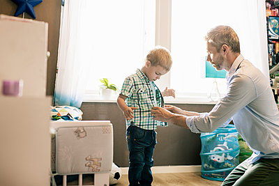 Father dressing up son in brightly lit room at home on sunny day - p426m1179361 by Kentaroo Tryman