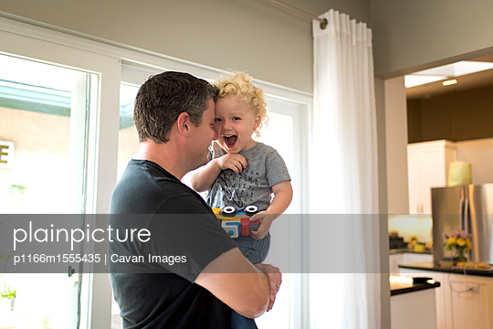 Portrait of cheerful son carried by father at home - p1166m1555435 by Cavan Images