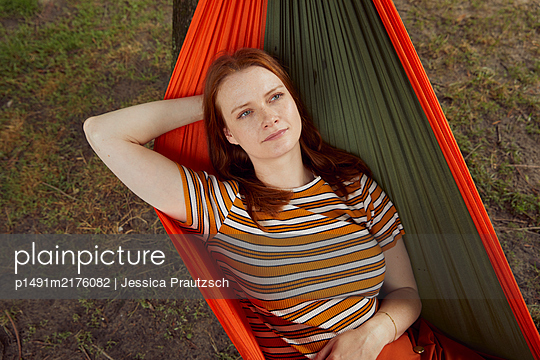 Red-haired woman relaxing in a hammock - p1491m2176082 by Jessica Prautzsch