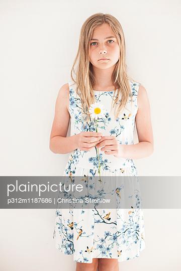 Girl holding flower - p312m1187686 by Christina Strehlow