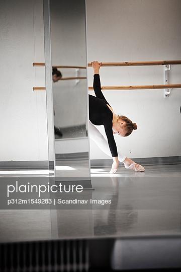 Ballet dancer stretching while exercising