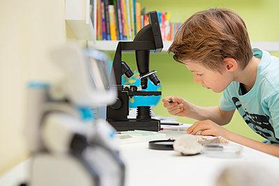 Junger Schüler arbeitet mit dem Mikroskop - p105m2064097 von André Schuster