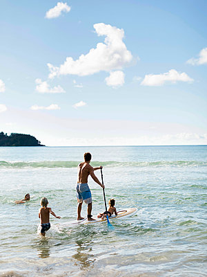 Man on paddleboard with his children at beach - p1427m2109760 by Jessica Peterson