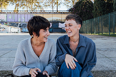 two young women sitting on stair and laughing, Seville, Spain - p300m2252417 von Julio Rodriguez