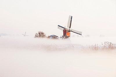 Old fashioned windmill in misty landscape - p429m802934f by Arno Masse