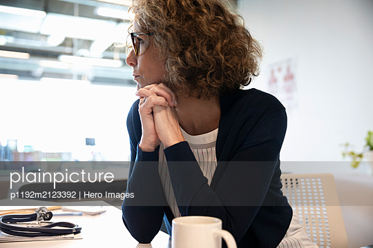 Portrait of mature female medical consultant with hands clasped - p1192m2123392 by Hero Images