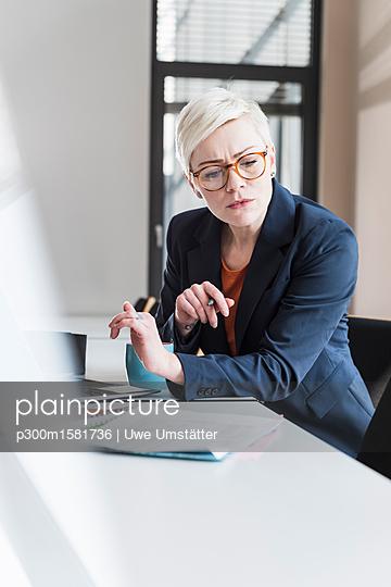 Businesswoman working at desk in office - p300m1581736 von Uwe Umstätter