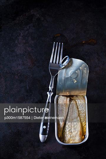 Opened sardine can and fork on dark ground - p300m1587554 von Dieter Heinemann