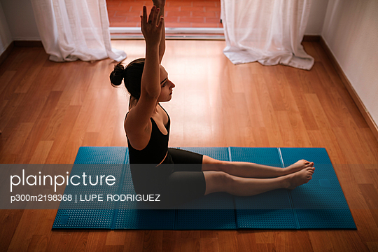 Young woman with arms raised exercising while sitting on mat at home - p300m2198368 by LUPE RODRIGUEZ