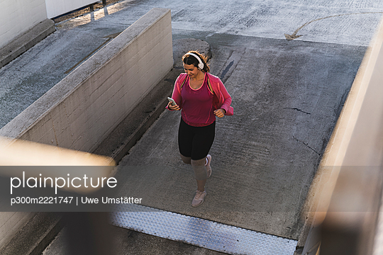 Young woman using mobile phone while running on terrace at sunset - p300m2221747 by Uwe Umstätter
