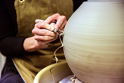 Close up of potter wearing apron working on spherical clay vase on pottery wheel. - p1100m1575712 by Mint Images