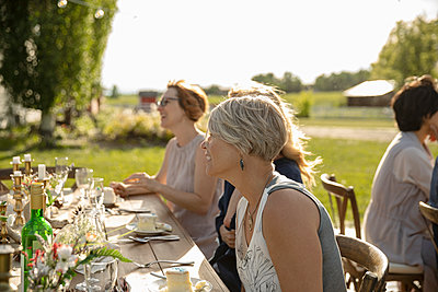 Smiling woman eating cake at garden party table - p1192m2009276 by Hero Images