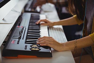 Female sound engineer working in office - p1315m1422210 by Wavebreak