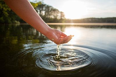 Junge Frau lässt Wasser durch die Finger laufen - p1396m1442038 von Hartmann + Beese