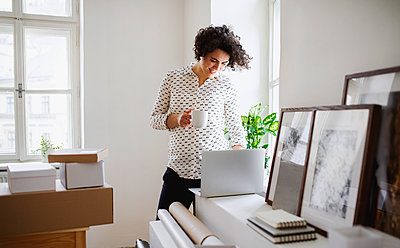 Smiling young woman with coffee cup working on laptop at desk - p300m2143836 by HalfPoint