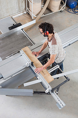 High angle view of carpenter using a sliding table saw in workshop - p301m1070058f by Halfdark