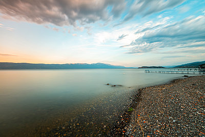 Scenic view of Lake Ohrid against cloudy sky, North Macedonia - p623m2271904 by Pablo Camacho