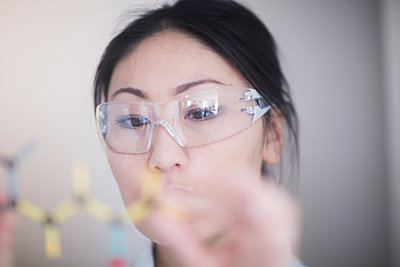 Asian woman scientist analysing molecule model in a laboratory. - p924m2165006 by Sigrid Gombert