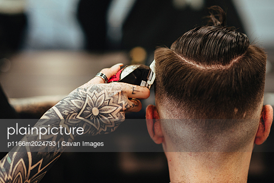 Cropped hand of female barber cutting male customer's hair in salon - p1166m2024793 by Cavan Images