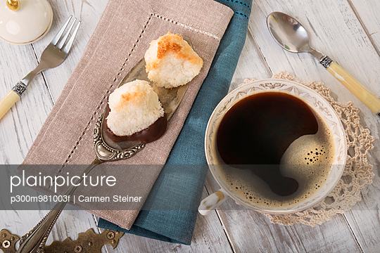 Two coco macaroons on cake server and cup of black coffee, elevated view - p300m981003f by Carmen Steiner