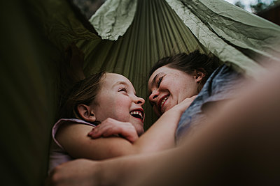 Siblings hugging and smiling in hammock outside - p1166m2201362 by Cavan Images