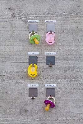 Pacifiers hanging on concrete wall with name tags - p300m1130053f von Werner Dieterich