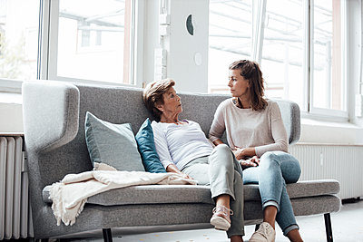 Relaxed senior woman talking with granddaughter while sitting on sofa at home - p300m2274901 by Gustafsson