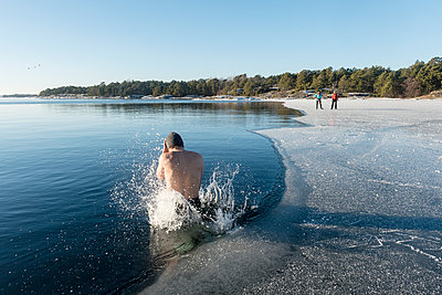 Man jumping into freezing cold water - p312m1472698 by Fredrik Schlyter