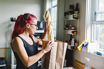 Young woman with pink hair unpacking baguette from shopping bag in kitchen - p924m1180141 by Lena Mirisola