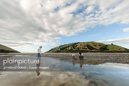 Children playing in shallow water at low tide in New Zealand - p1166m2130649 by Cavan Images