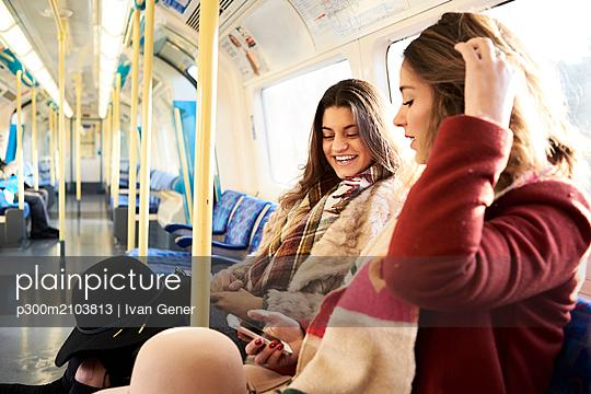 UK, London, two happy women in underground train using cell phone - p300m2103813 von Ivan Gener