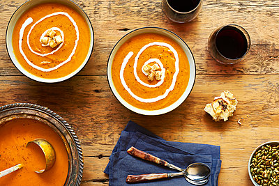 High angle view of squash soup served on wooden table - p1166m1508435 by Cavan Images