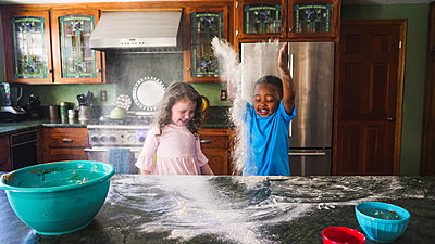 Boy and girl throwing flour in the air - p1166m2090686 by Cavan Images