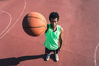 Young basketball player holding ball - p300m1580893 by Francesco Morandini