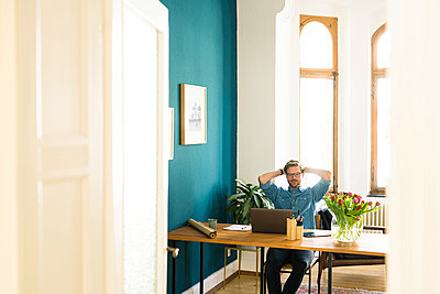 Casual businessman in home office working at his laptop - p300m2084023 by Steve Brookland