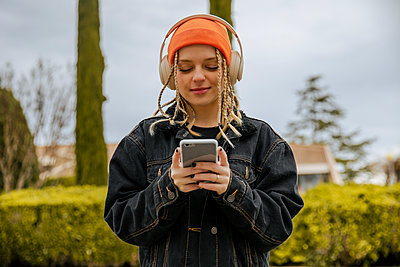 Portrait of a blonde girl with braids and blue eyes wearing a hat listening to music with the mobile phone and headphones. Lleida, Spain. - p300m2242254 von Aitor Carrera Porté