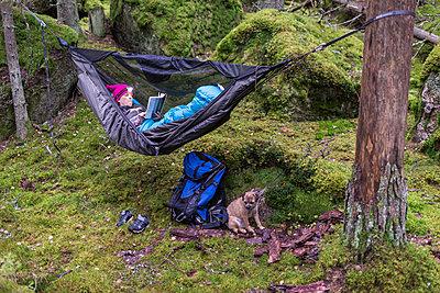 Woman reading book in hammock in forest - p312m2049909 by Fredrik Schlyter