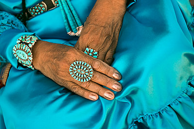Lap of woman wearing traditional blue dress and rings - p555m1301832 by Julien McRoberts