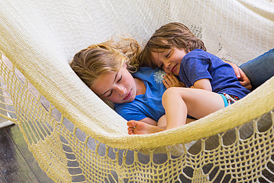Caucasian brother and sister cuddling in hammock - p555m1490983 by Marc Romanelli