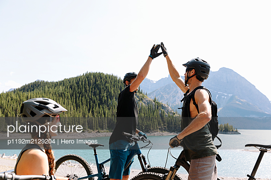 Friends mountain biking, high fiving at sunny lakeside - p1192m2129204 by Hero Images