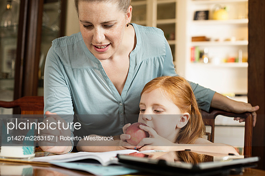 Mid adult mother helping daughter with homework at dining room table - p1427m2283157 by Roberto Westbrook