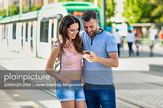 Couple looking at smartphone while waiting for tram at the station - p300m2012658 von Javier Sánchez Mingorance
