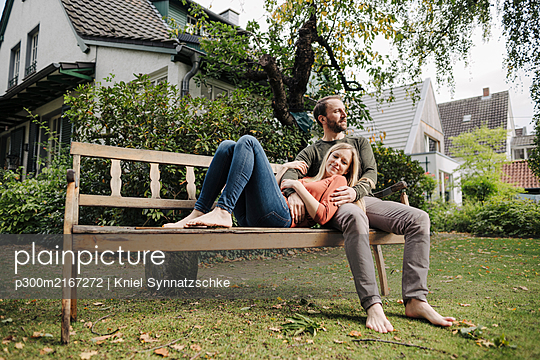 Couple relaxing on bench, enjoying nature in their garden - p300m2167272 by Kniel Synnatzschke