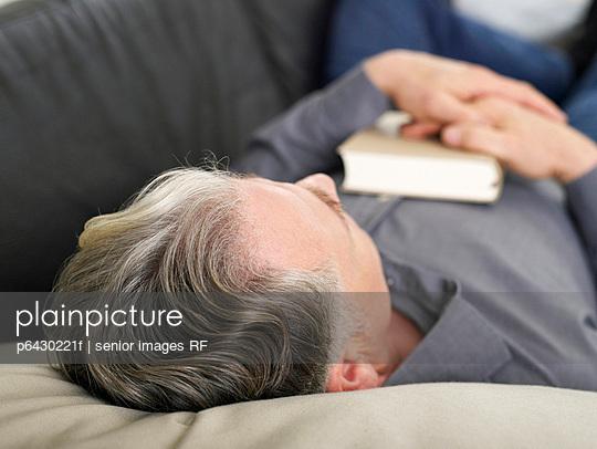 Aelterer Mann schlaeft auf dem Sofa  - p6430221f von senior images RF