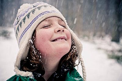 Sweden, Girl enjoying snow falling onto her face - p1687m2284253 by Katja Kircher