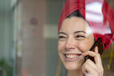 Portrait of happy woman with head wrapped in a towel talking on the phone behind windowpane - p300m2170642 by Robijn Page