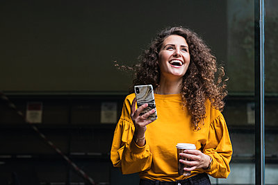 Cheerful female professional with curly hair laughing while holding mobile phone and disposable cup - p300m2241609 by NOVELLIMAGE