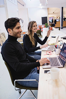 Cheerful young woman and man looking away while sitting at desk in office - p426m1407181 by Maskot